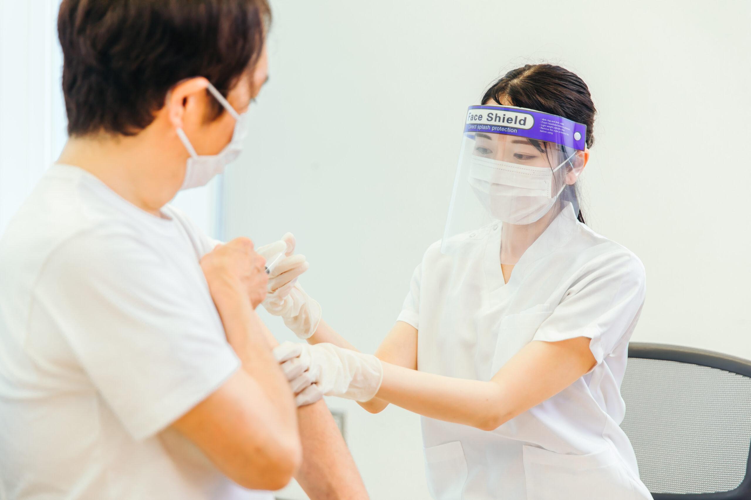 男性にワクチン接種を行う女性の写真