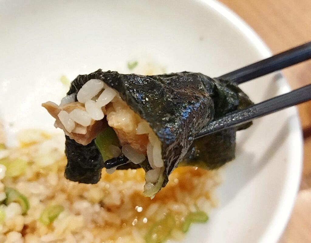 「銀家 日吉本店」のラーメンのネギチャーシュー丼をのりで巻いて食べているときの写真