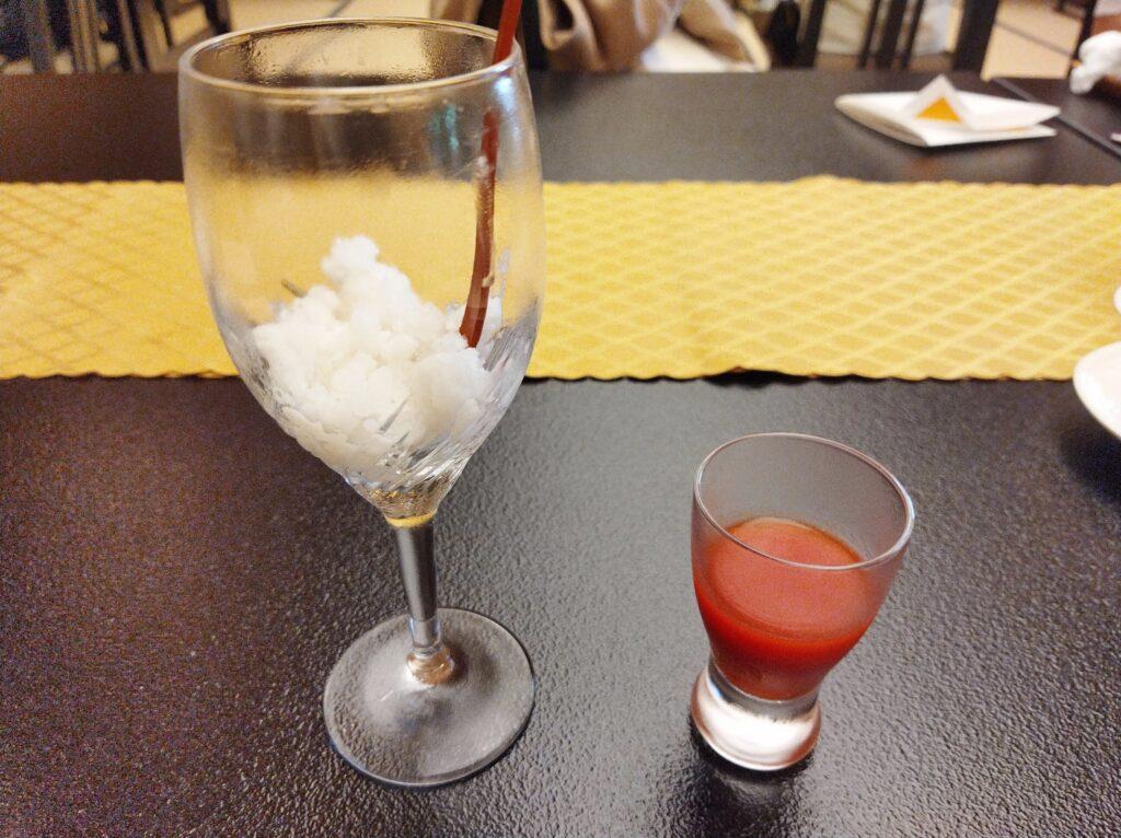 グラスにあまざけのフローズンが入っており、横には小さいグラスに入ったトマトジュースが置かれている