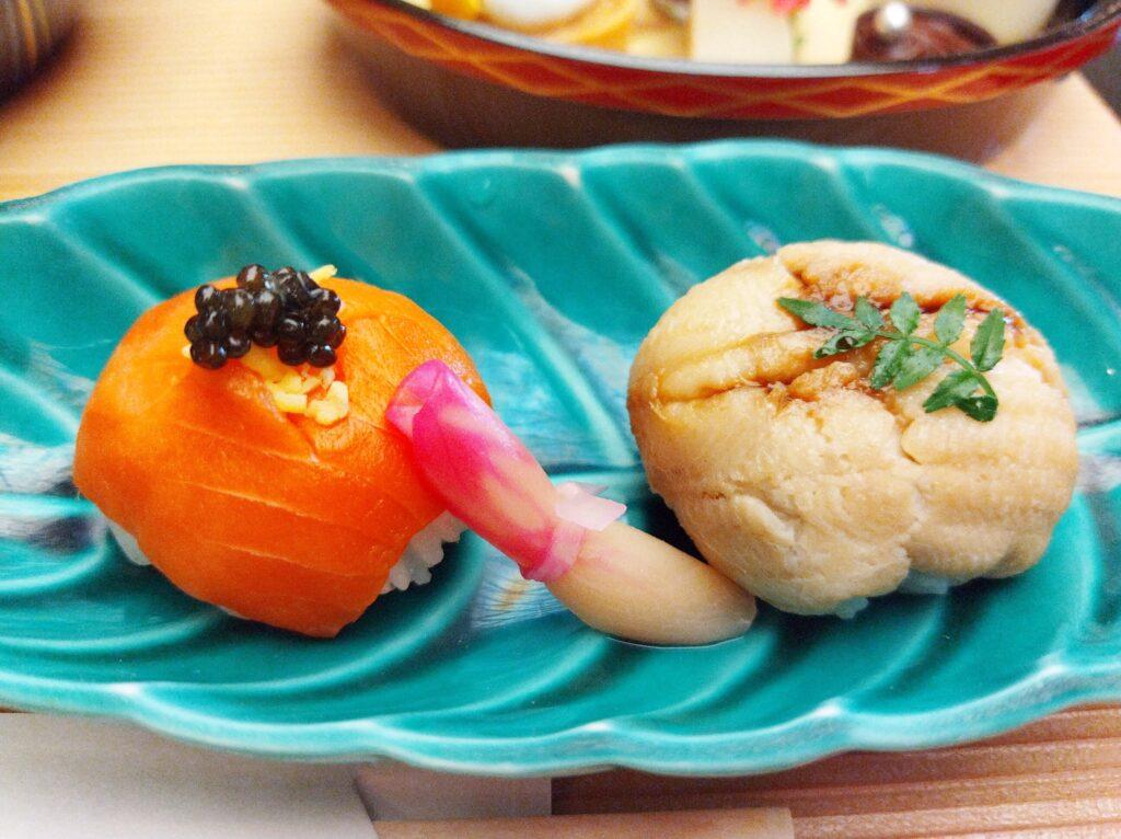 青っぽい細長い皿にサーモンと穴子の手毬寿司が1貫ずつ載っている。中央には生姜